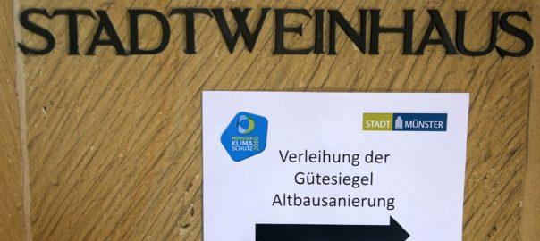 Schriftzug Stadtweinhaus auf Sandsteinaussenfassade, dadrunter Zettel mit Hinweis auf die Veranstaltung Verleihung Gütesiegel Altbausanierung