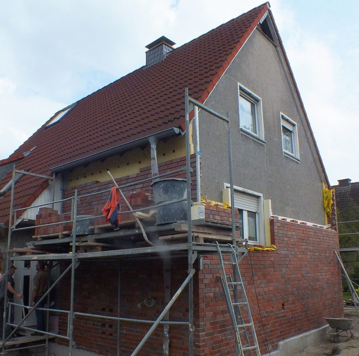 Baustelle eines Einfamlienwohnhaus, von unten hoch wird der alte verputzte Bau neu verklinkert und gedämmt