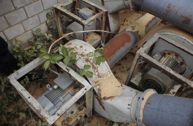 alte Pumpe liegt verrostet und verstaubt im Unkraut