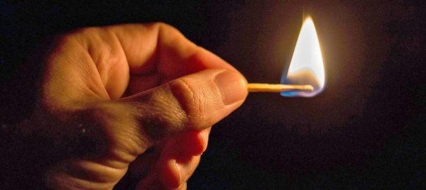 Hand mit brennendem Streichholz