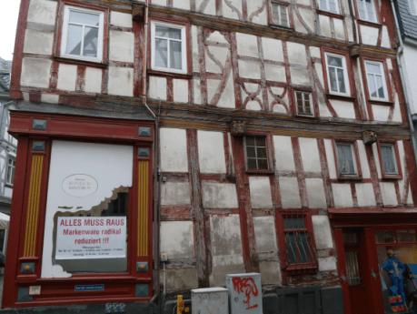 Unsanierte Fachwerkhauszeile in historischer Altstadt, gewerbliche Nutzung offensichtlich nicht lukrativ, Schild mit Ausverkauf, Fassade am Verfallen