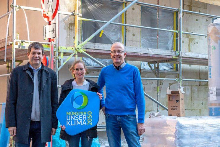 Drei Personen vor dem eingerüsteten Mehrfamilienhaus: Von links Andreas Deppe vom Planungsbüro ENTECH, Nadine Somberg von der Stadt Münster und der Bauherr