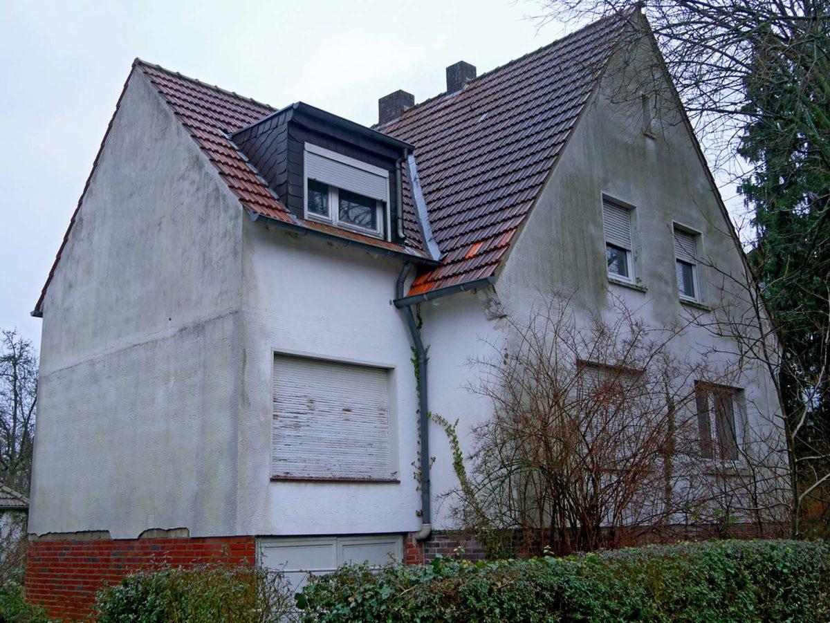 Sanierungsbedürftiges Zweifamilienhaus mit Flecken und Algenbewuchs auf dem hellen Putz